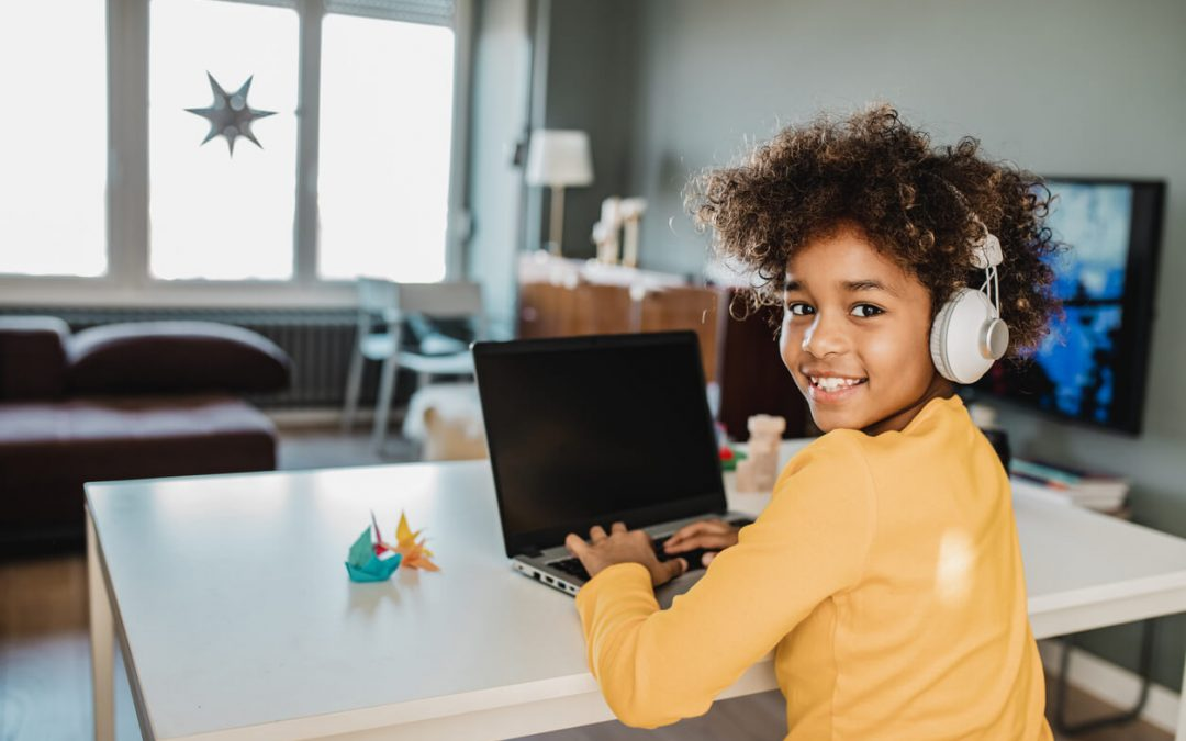 Young African american girl at home sitting on the table wearing headphones, using laptop, studying and looking at camera